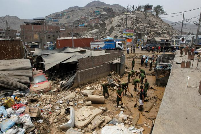 Peruvian soldiers help remove mud from affected houses after a landslide in San Juan de Lurigancho distritct in Lima